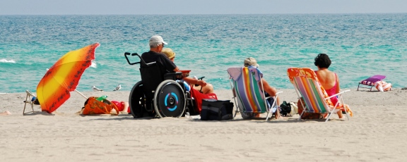 Photo of family including person in a wheelchair on the beach
